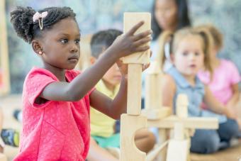 Girl Stacks Blocks at Preschool