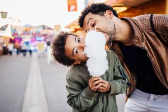 Playful father and son sharing candy floss at the fun fair