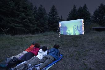 Young friends watching projection screen at campsite during night
