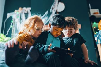 Three children sitting on a beanbag looking at a computer tablet