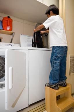 Young boy using the washing machine