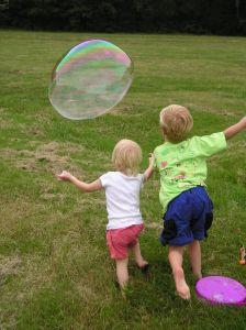 Image of children chasing their giant soap bubble