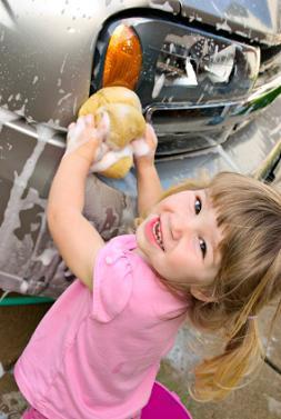 Little girl helping wash a car