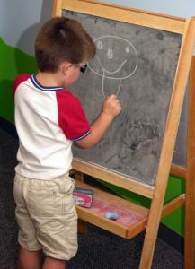 preschooler at chalkboard