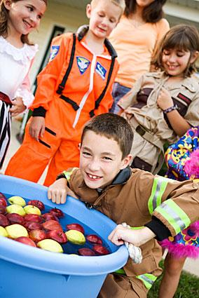 Kids bobbing for apples at a Halloween party