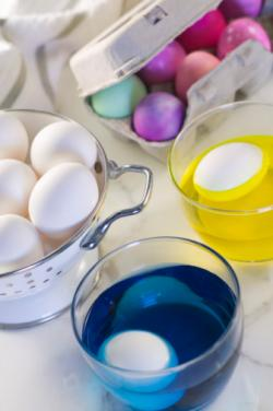 Dipping Easter eggs in dye