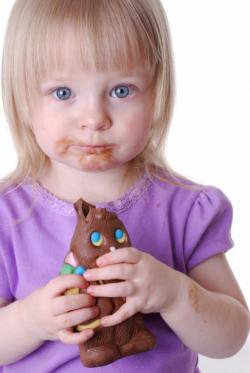 Toddler girl eating chocolate Easter bunny