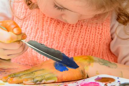 Child painting with feather