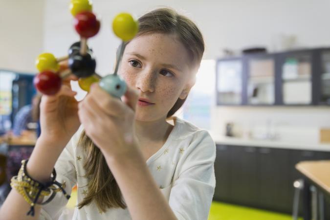 Student examining molecule model