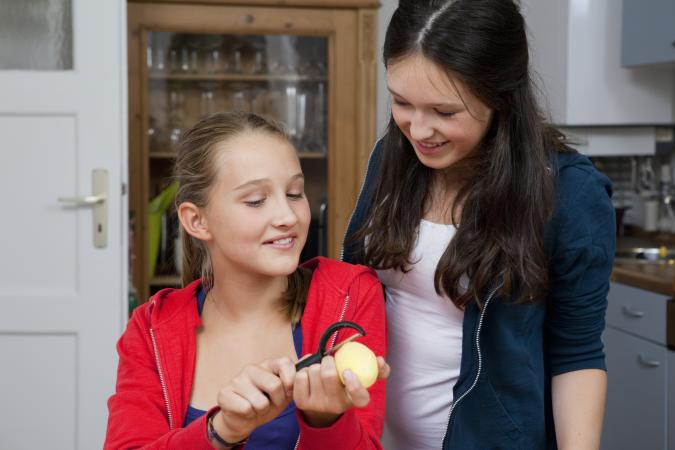 Girls peeling potatoes in kitchen