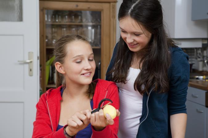 Girls peeling potatoes in kitchen