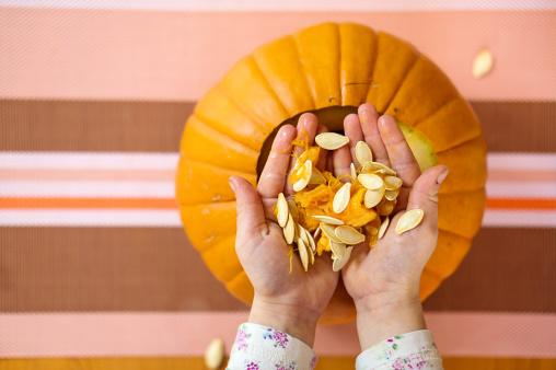 Hands removing seeds from a pumpkin