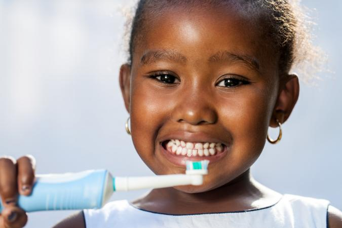 girl holding electric toothbrush