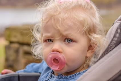 Baby girl with pacifier in mouth