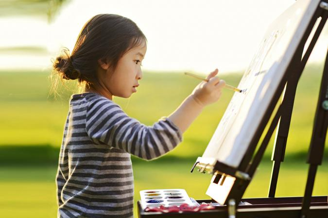 child using easel for painting