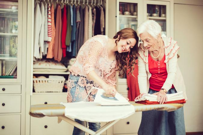 Teen helping senior woman with ironing