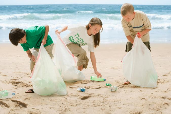 Kids picking up trash on beach