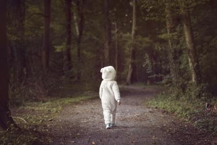 Small child wearing white bear suit in the woods
