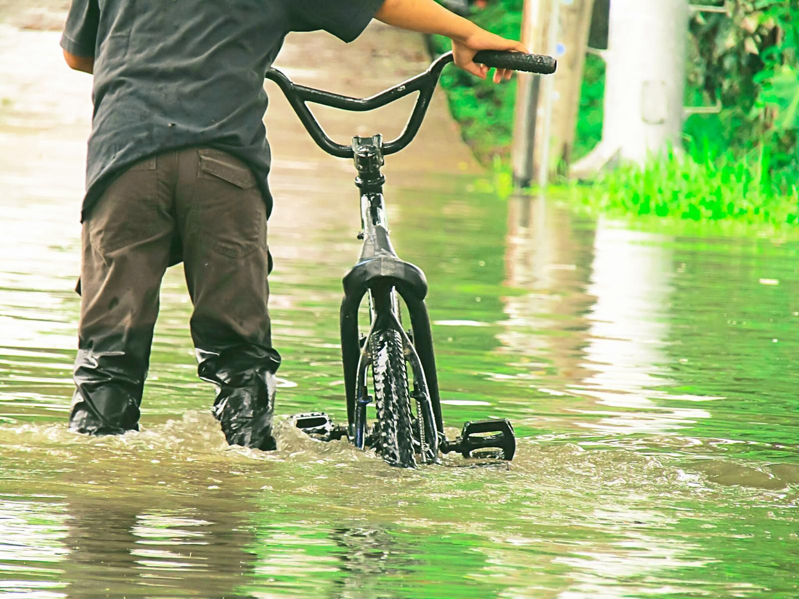 Man With Bicycle Standing In Water