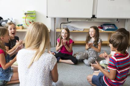 Teacher and pupils sitting on floor of their classroom