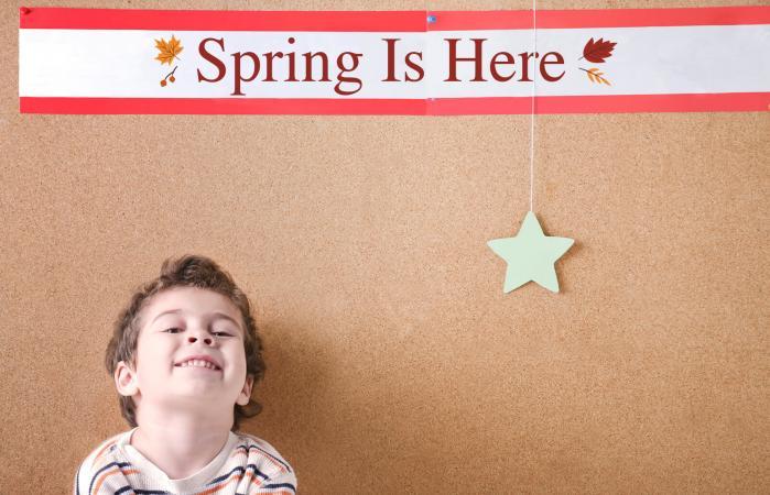 Kindergarten boy sits against a cork board