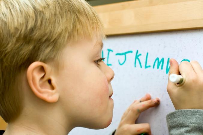 kid writing alphabet