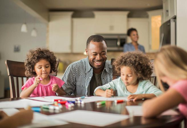 Father and children drawing in kitchen