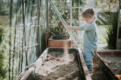 Girl digging in soil in greenhouse