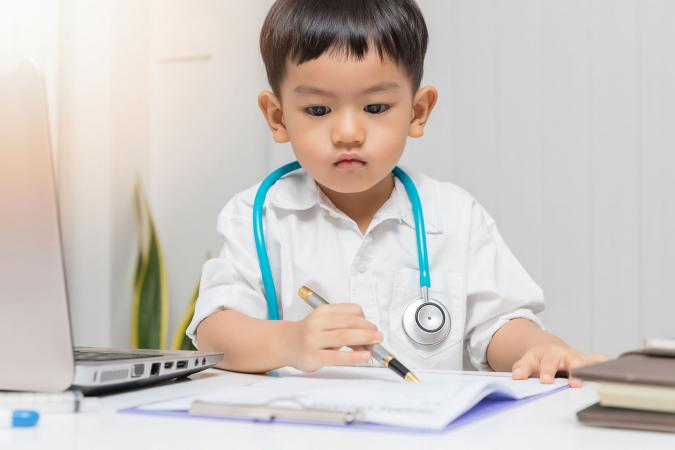 Young asian boy playing doctor