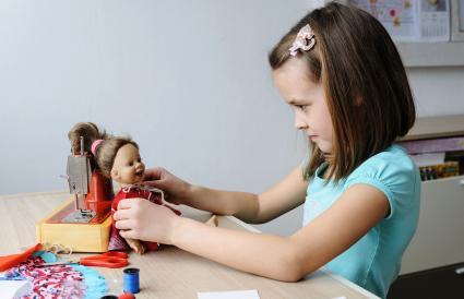 Girl dressing the doll