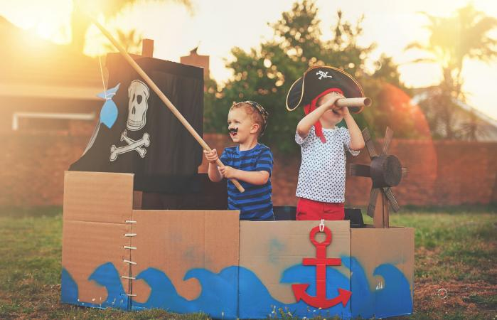 Boys playing pirates in a cardboard ship
