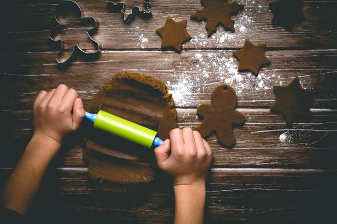 Child rolling out gingerbread cookie dough