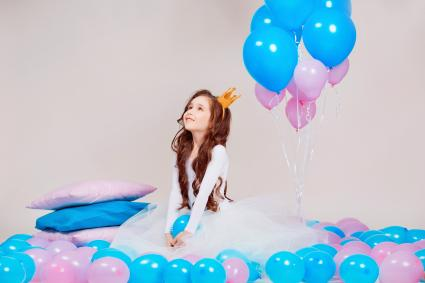 Cute little princess girl sitting among balloons