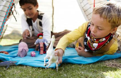 Boys playing with animals in a tent