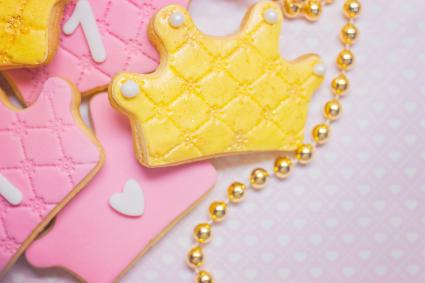Crown shaped royal icing cookies on pink background