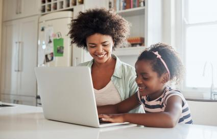 mother and daughter using a laptop together