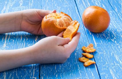 Children's hands peeling tangerine