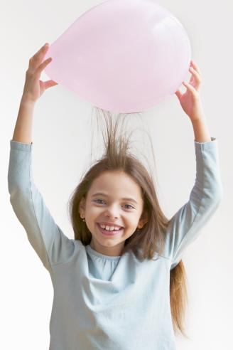 Girl creating static in hair with balloon