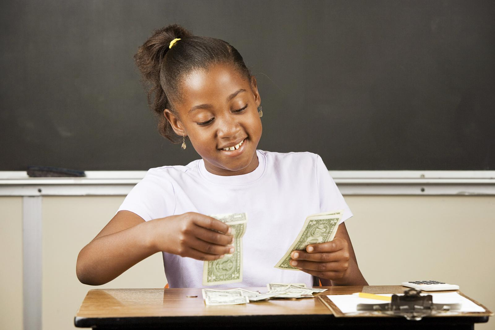 Student counting money on a desk