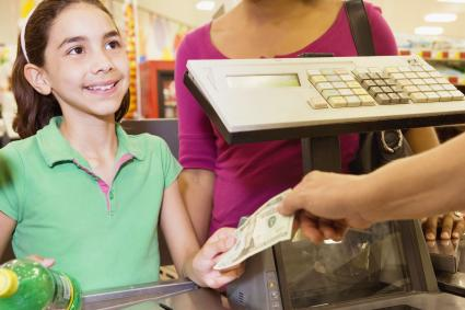 Young Shopper Giving Money to the Cashier