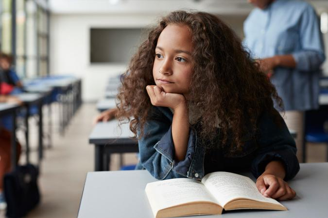 girl in class with book thinking