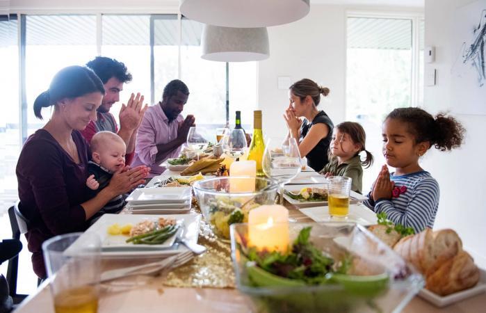Family praying during thanksgiving dinner