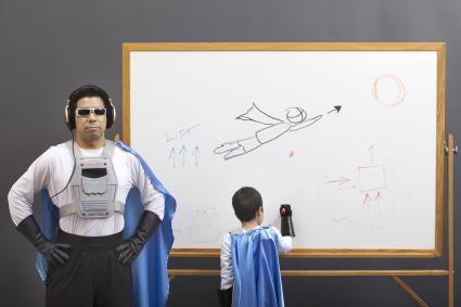 Kid writing in a whiteboard dressed as superman