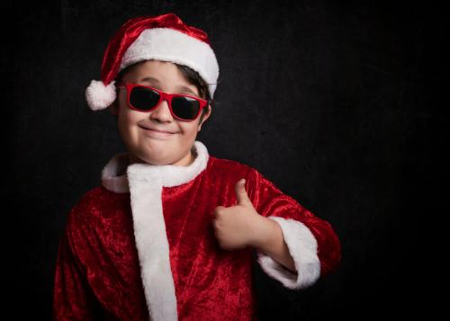 boy with sunglasses dressed as Santa