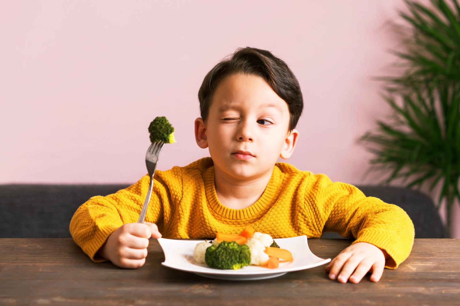 Kid eating a plate full of vegetables