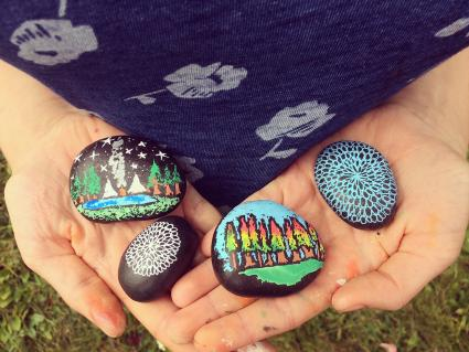 holding painted rocks in hands