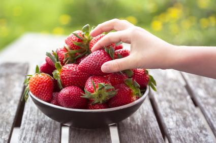 Girl's hand taking strawberry