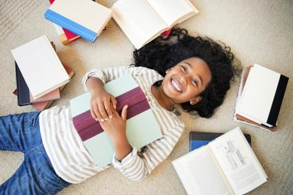 Girl laying on floor with books