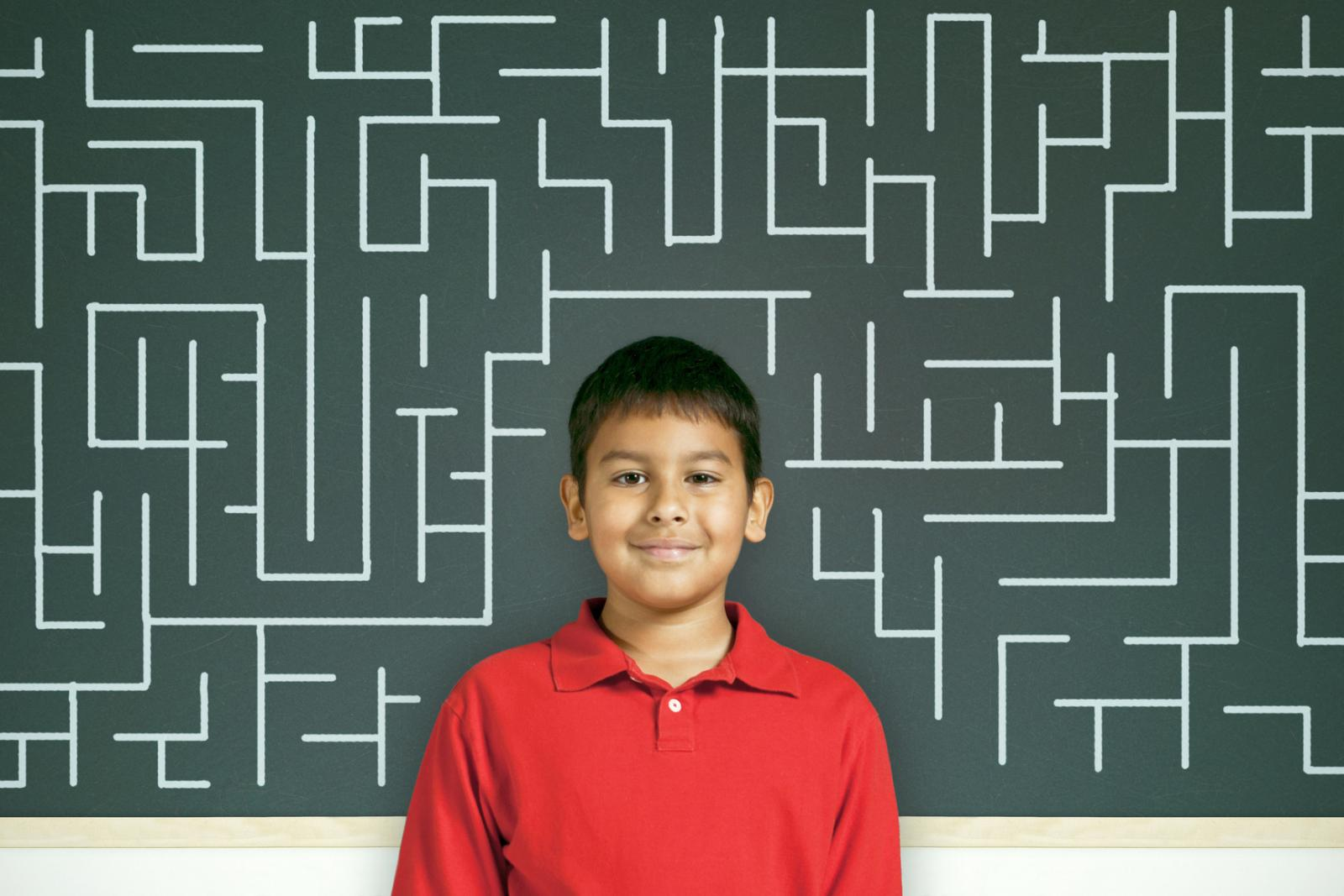 Child by chalkboard with maze