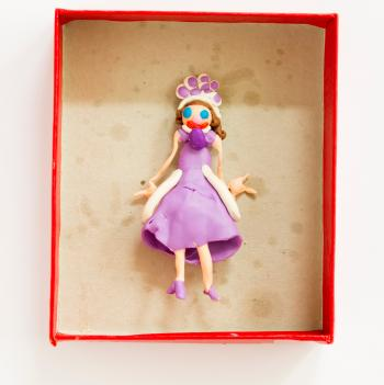 Clay doll sculpture in cardboard box